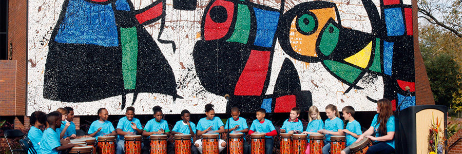 Many young students playing drums in front of the Miro mosaic