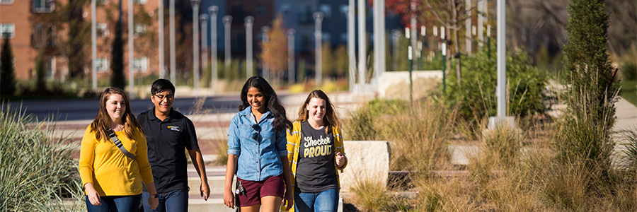 Four students walking from campus housing to class